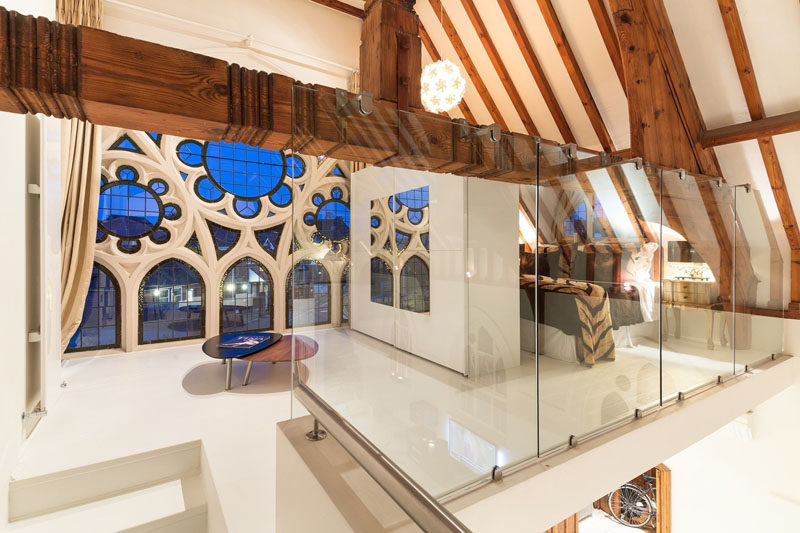 Upstairs and at one end of this renovated church is a bedroom that overlooks the living area below and takes advantage of the light from the original windows. #RenovatedChurch #ChurchConversion #WoodBeams #ModernBedroom #InteriorDesign #Windows