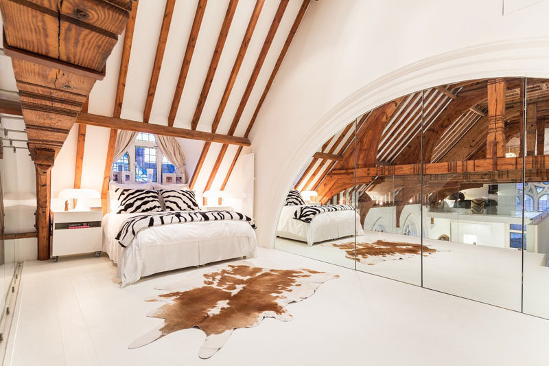 This modern bedroom in a renovated church features a wall of mirrors to reflect the interior. #RenovatedChurch #ChurchConversion #WoodBeams #ModernBedroom #InteriorDesign #Mirrors