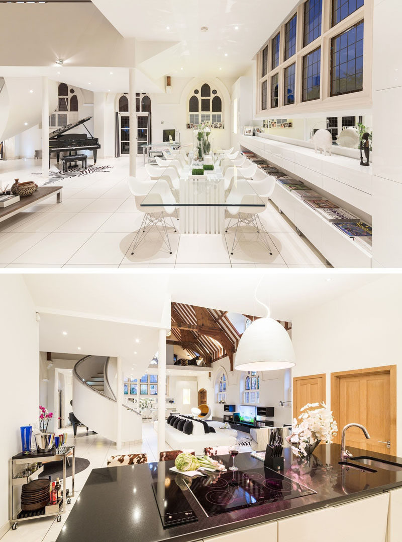 This church conversion has a modern dining room with a glass dining table with room for 12 people, and the kitchen has an island with a cooktop, sink and dark countertop. #ChurchConversion #DiningRoom #ModernKitchen #ModernInterior