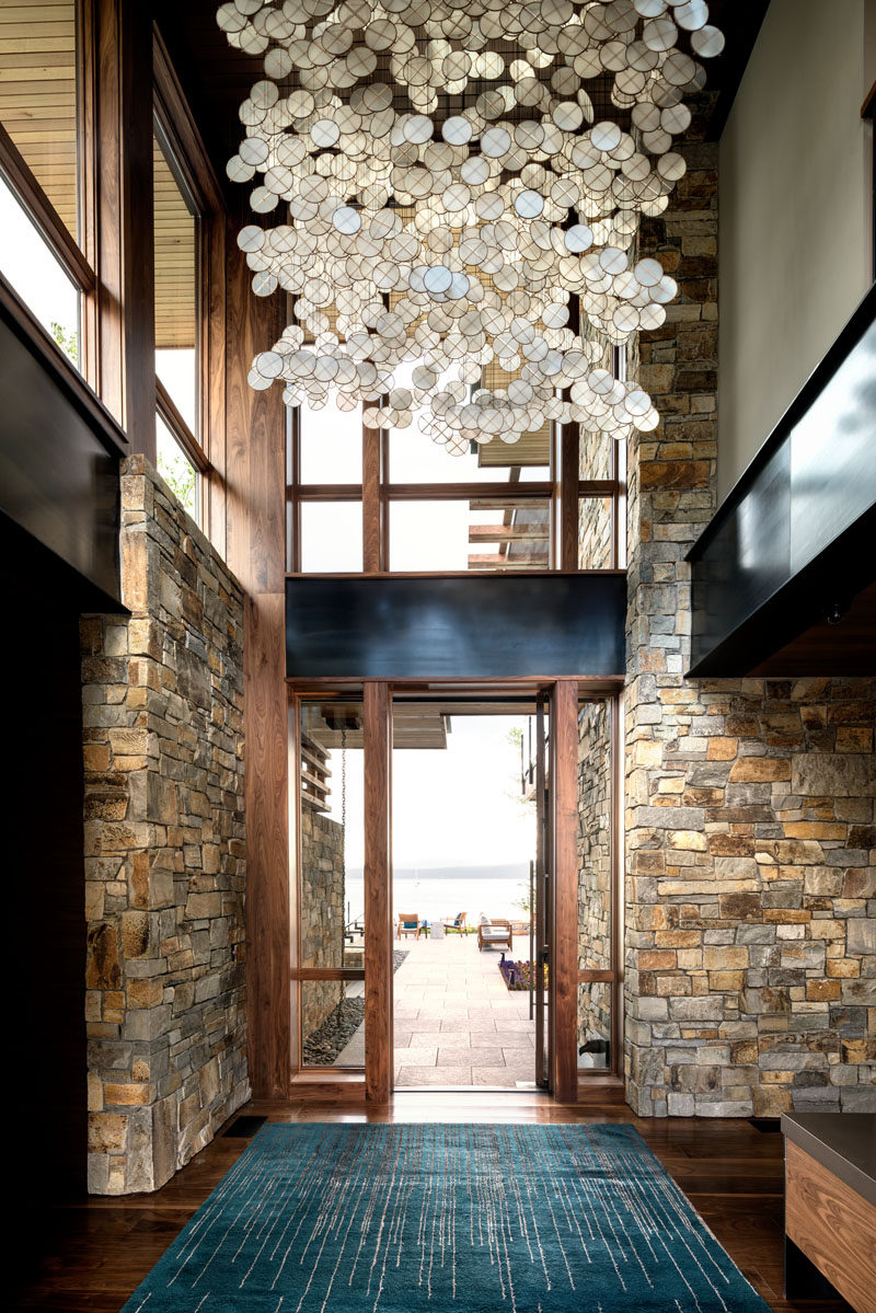 Stepping inside into this contemporary entryway, you can see straight through to the lake.