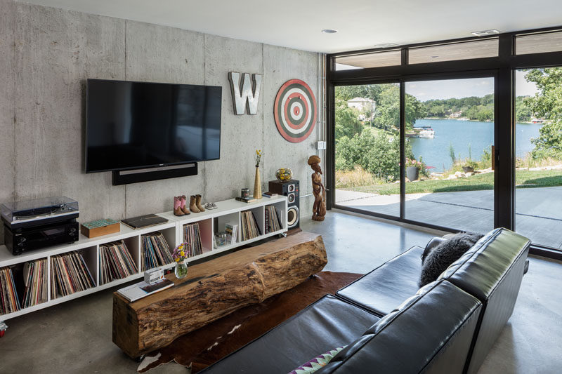This modern lakeside house has tv room with a raw concrete wall on the lowest level of the house, and it also has direct access to the backyard.