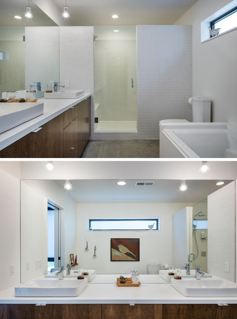 In this master bathroom there's a large vanity with dual sinks and plenty of storage, while a glass door and partial wall separates the shower from the rest of the space.
