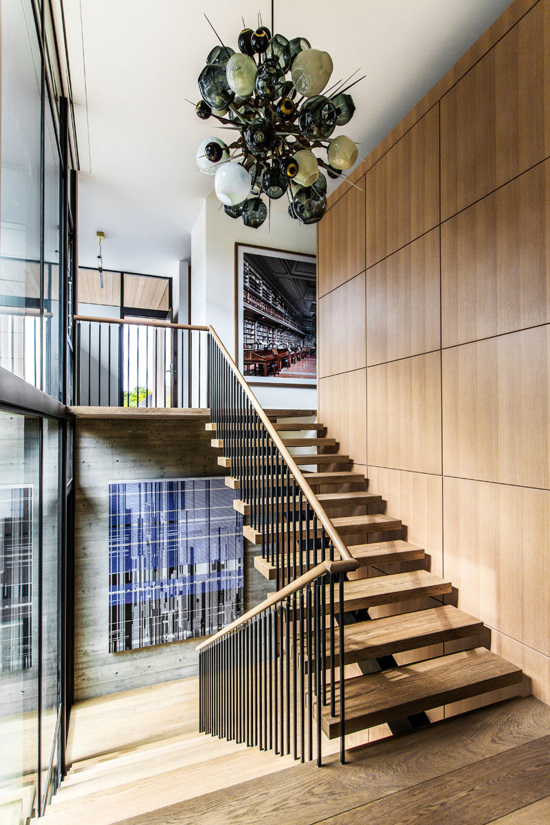 Wood and steel stairs lead up to the upper floor of this modern house.