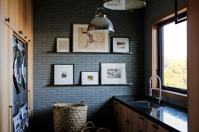 In this modern laundry room, wood cabinets surround the washer and dryer, while grey tile becomes a backdrop for some shelving that displays art.
