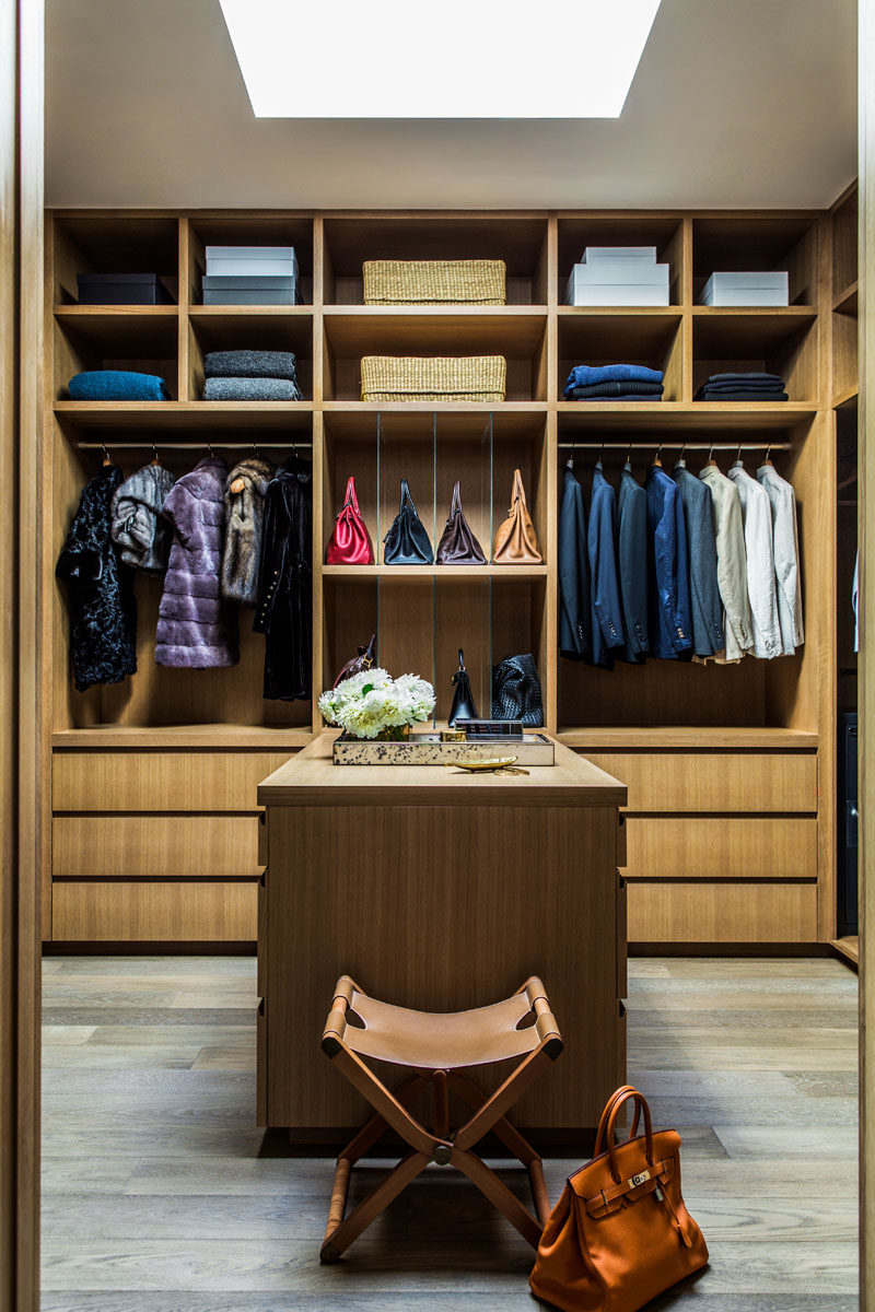This modern walk-in closet with a skylight is filled with plenty of open shelving, cabinets and an accessory island. #WalkInCloset #ClosetIdeas