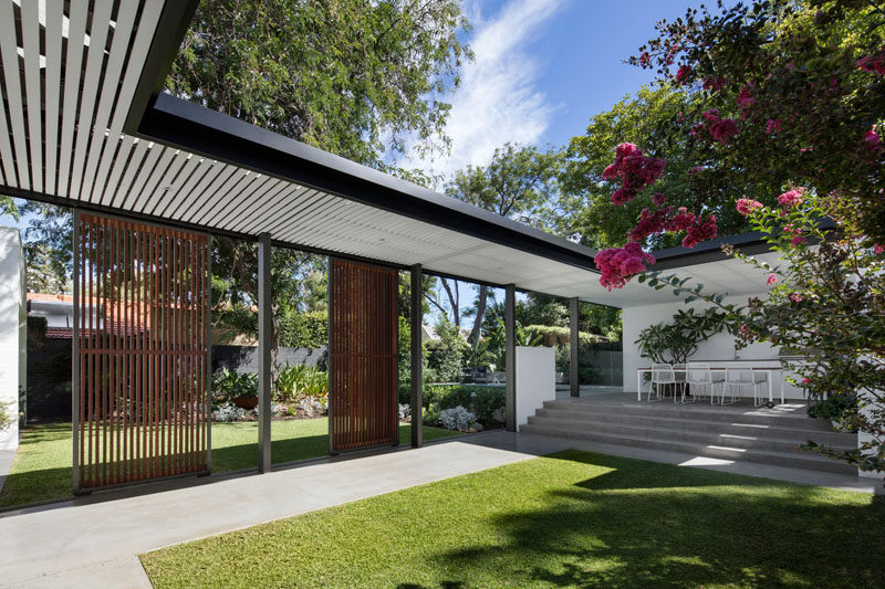 This modern backyard has a covered walkway that connects the house to a raised outdoor kitchen / dining area and pool..