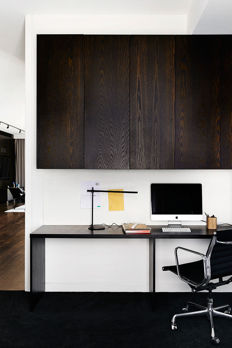 This small and modern office area has built-in dark wood cabinets and a desk large enough for two people.
