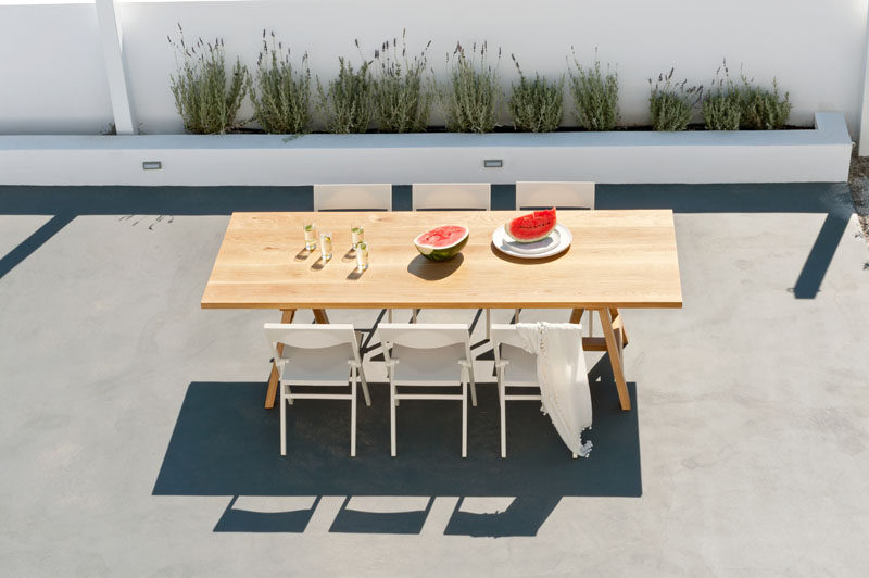 This modern house has an alfresco dining area with a large wood table and white chairs. #OutdoorDining #OutdoorSpace #AlfrescoDining