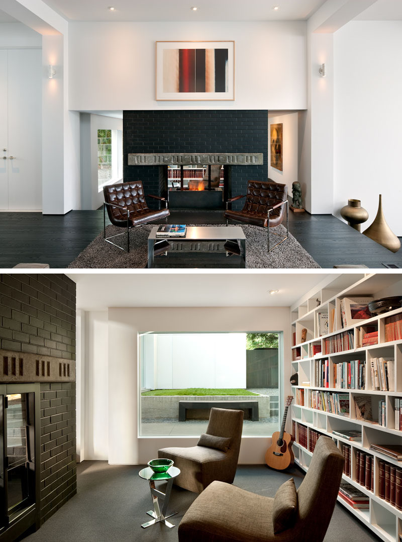 This dark brick double-sided fireplace can be enjoyed from the living room or from the library. #Fireplace #LivingRoom #Library #Shelving #InteriorDesign #DoubleSidedFireplace