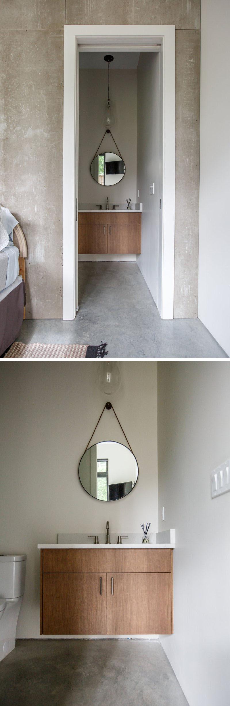 This simple en-suite bathroom has a wood vanity with a white counter and a hanging round mirror. #BathroomDesign #InteriorDesign #Bathroom #ModernBathroom