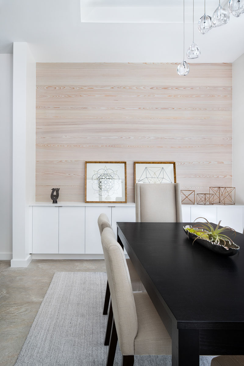 Light wood has been used as an accent wall in this contemporary dining room. Built-in white cabinets provide additional storage and acts as a space to display art and decorative items. #DiningRoom #LightWood #WoodAccentWall #InteriorDesign