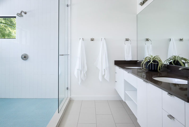 In this modern master bathroom, a large double-sink vanity with plenty of storage runs the length of the wall, while the shower is partitioned off with a glass shower screen. #MasterBathroom #ModernBathroom #BathroomDesign #Bathroom