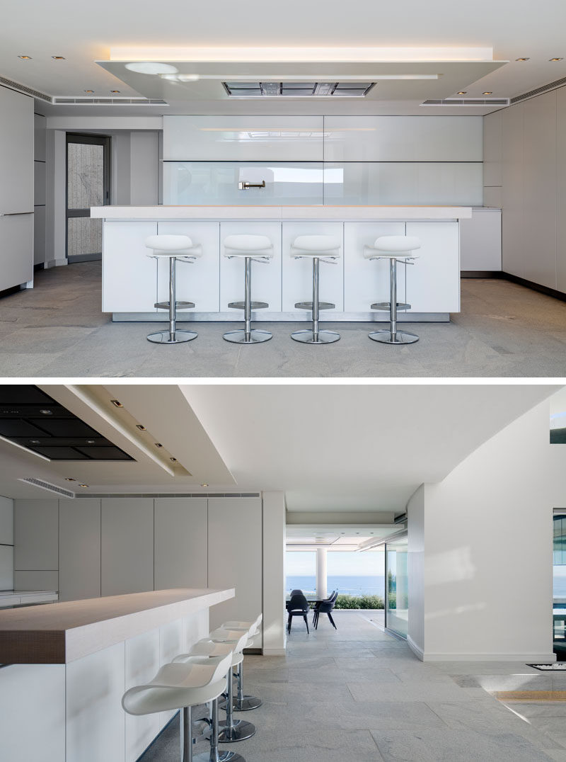 This modern house has a minimalist kitchen that has a light, neutral palette with white walls and cabinets, and grey floors. #MinimalistKitchen #WhiteKitchen #KitchenDesign