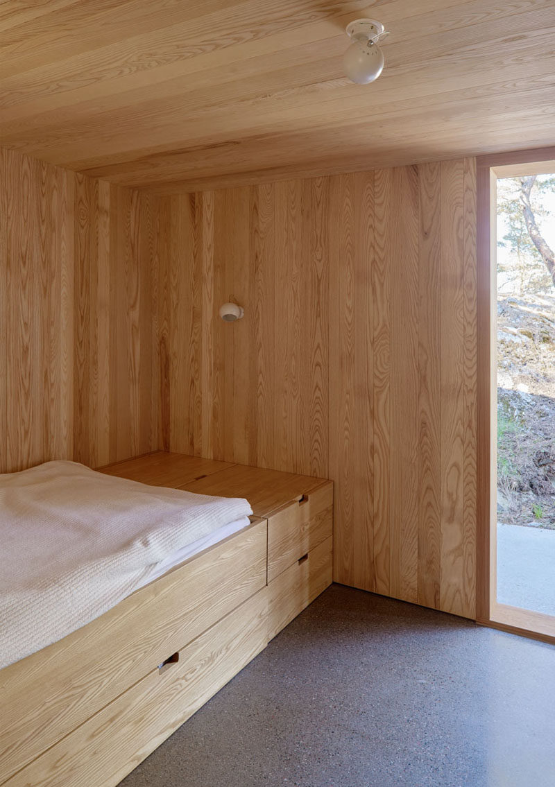 In this wood-lined Scandinavian bedroom, the bed has been raised to allow for storage or a pull-out bed, and simple globe-like lighting has been installed in the ceiling and on the wall. #ModernBedroom #Minimalist #Scandinavian #Wood