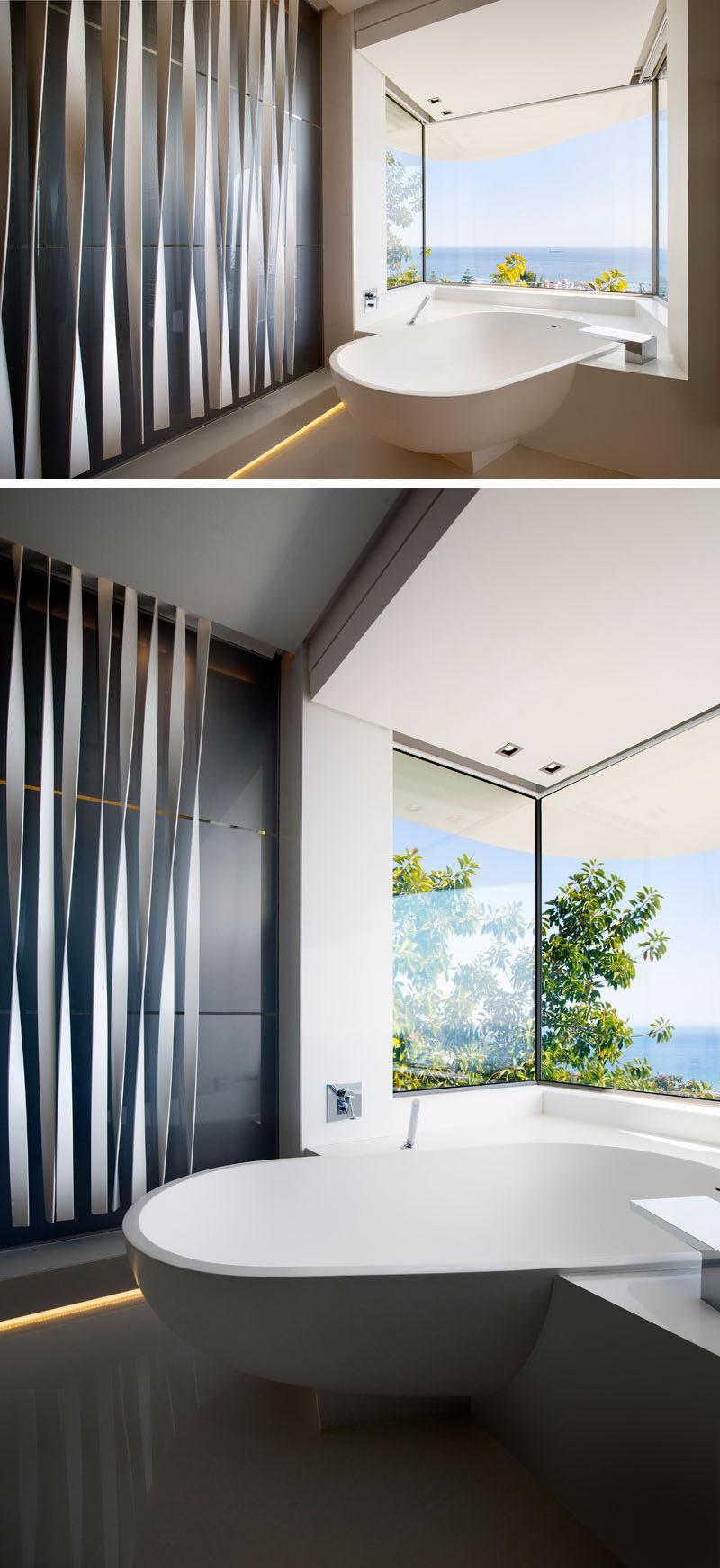 The master en-suite bathroom has been designed to strategically place a built-in bath tub that projects forward and allows 180 degree views over the ocean. #BuiltInBathtub #ModernBathroom #Windows #ModernBathtub