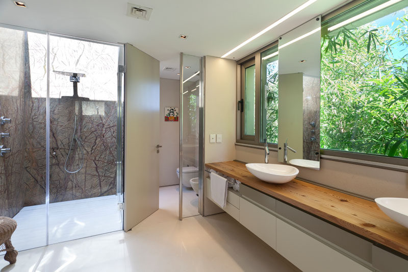 In this modern master bathroom, a large wood vanity looks out to the garden, while the glass enclosed shower has a skylight. #MasterBathroom #DoubleVanity #GlassEnclosedShower #InteriorDesign