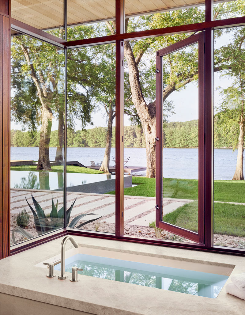 In this modern master bathroom, a deep soaking tub has plenty of windows that provide natural light and views of the lake. #Bathroom #SoakingTub #Windows #ModernBathroom