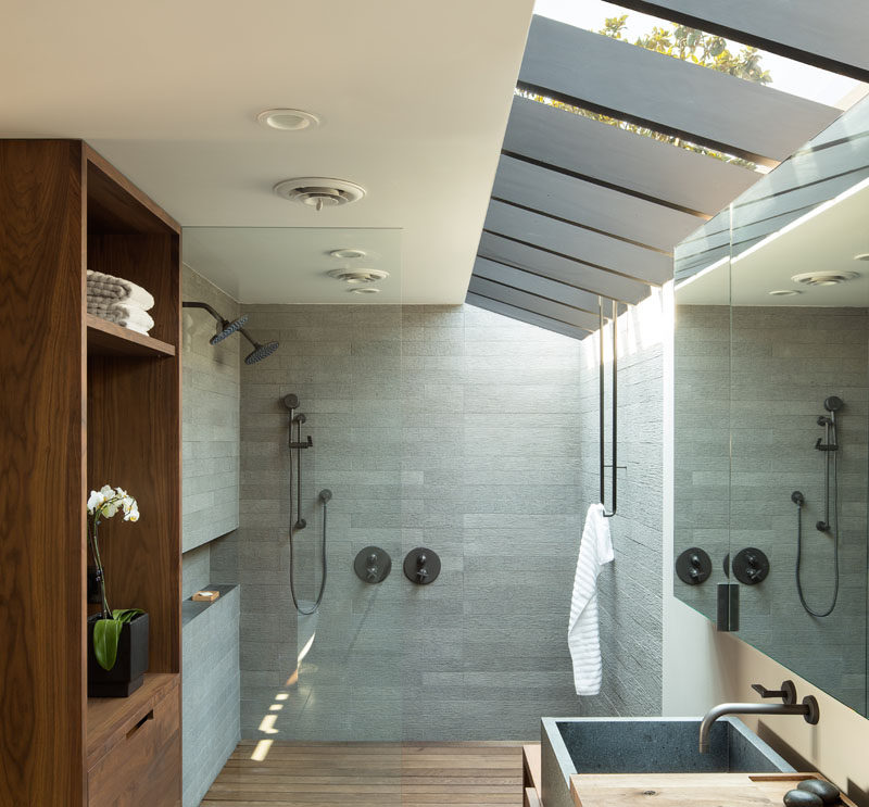 In this modern bathroom, a large skylight keeps the space feeling bright and open, while a glass shower screen separates the two person shower from the rest of the bathroom. #ModernBathroom #Skylight #ShowerForTwo #BathroomDesign