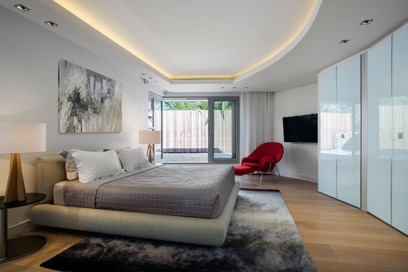 In this modern bedroom, hidden lighting highlights the curved outline of the recessed ceiling. #ModernBedroom #RecessedCeiling #HiddenLighting