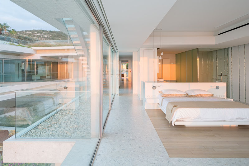 This modern bedroom has glass walls, a custom-designed bed and a floor with a wood inset that defines the bed location. #InteriorDesign #Bedroom #Flooring