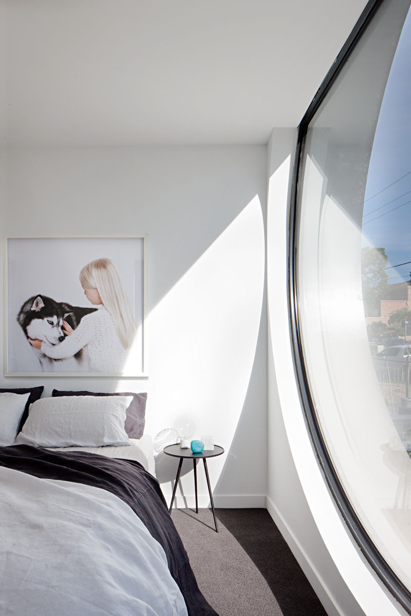 In this minimalist bedroom, a large porthole window provides plenty of natural light. #BedroomDesign #Window #InteriorDesign #ModernBedroom