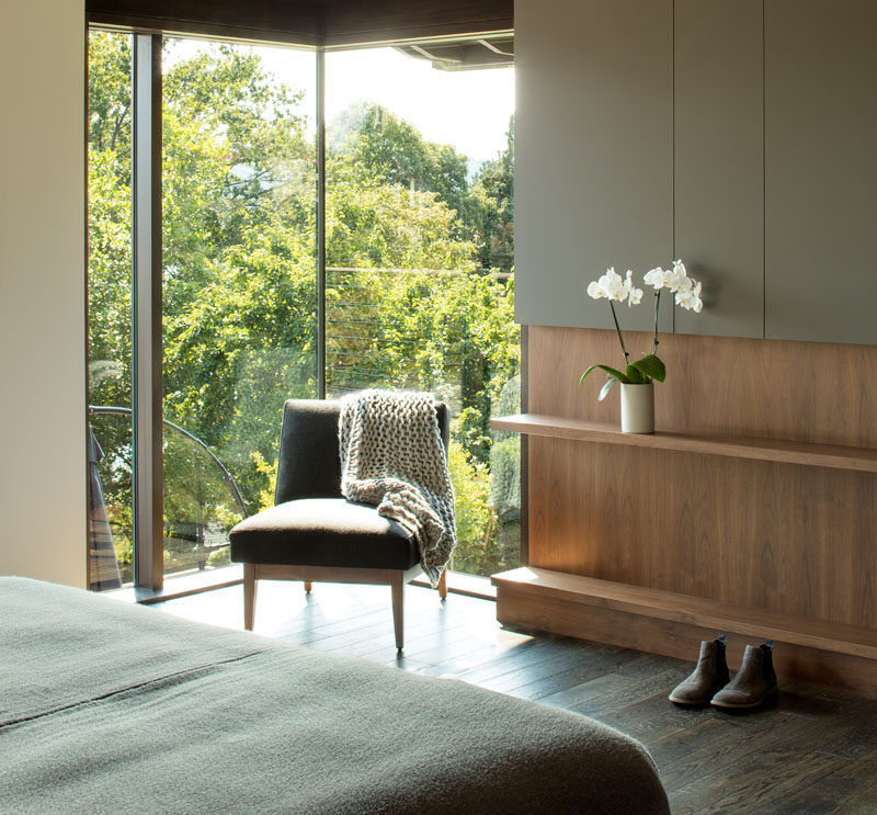 This modern bedroom has corner windows that provide natural light and views of the trees, while a built-in wood shelf allows for a touch of nature to be displayed inside. #ModernBedroom #Shelving #Windows