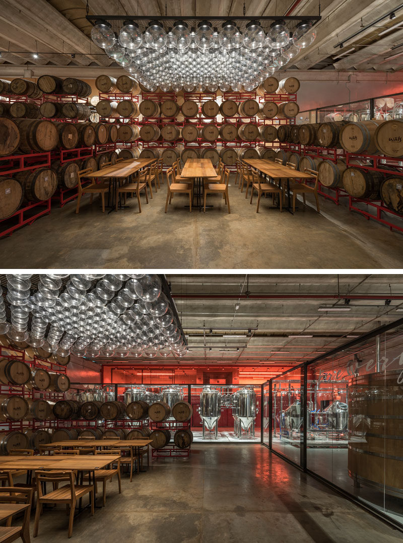 Inside this modern brewery, sets of wood tables set up for tastings are scattered among hundreds of wooden barrels that frame and divide the space. #Brewery #InteriorDesign