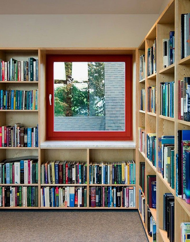 This home library has built-in wood shelves and a window with a bright red window frame. #Library #HomeLibrary #Shelving