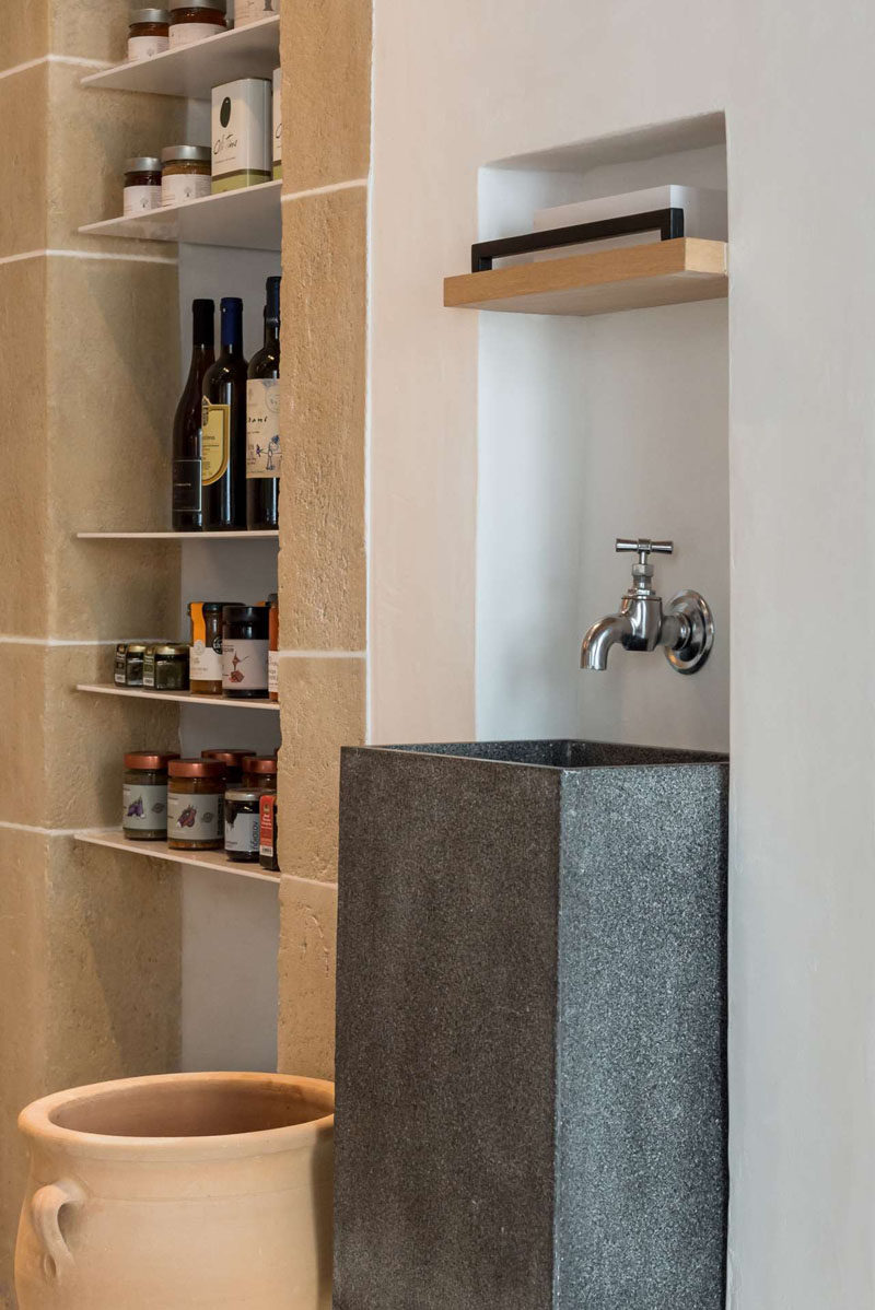 This contemporary cafe has built-in shelving with products for purchase and a tall grey sink with a single tap. #CafeDesign #CafeInterior #Cafe