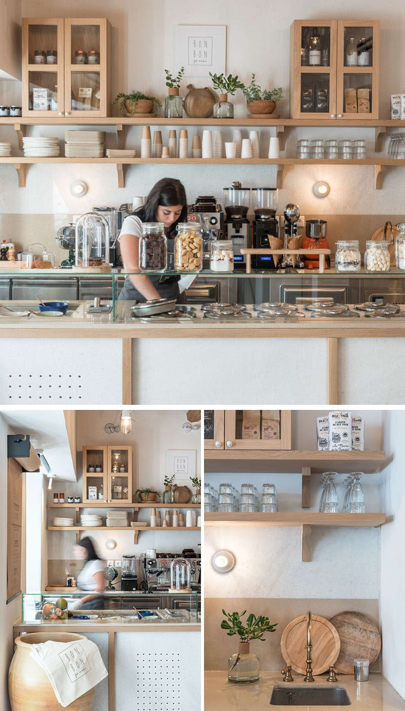 A wood and white color palette has been used throughout this modern cafe with simple wood shelves and cabinets providing storage for the variety of plates and cups. #Cafe #CafeInterior #RetailDesign #InteriorDesign