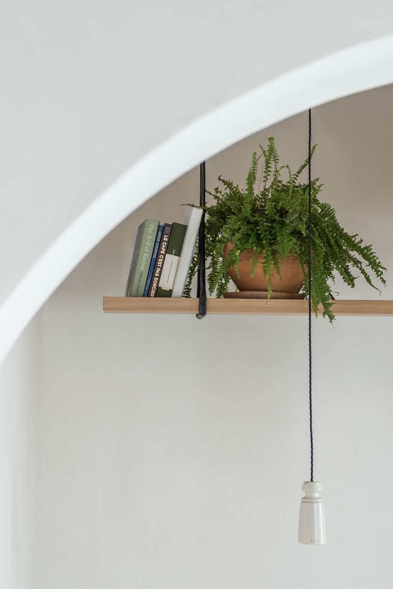 Hanging above a dining area in a modern cafe is a simple wood shelf that's home to plants and books. #Shelving #InteriorDesign #Shelf #HangingShelf