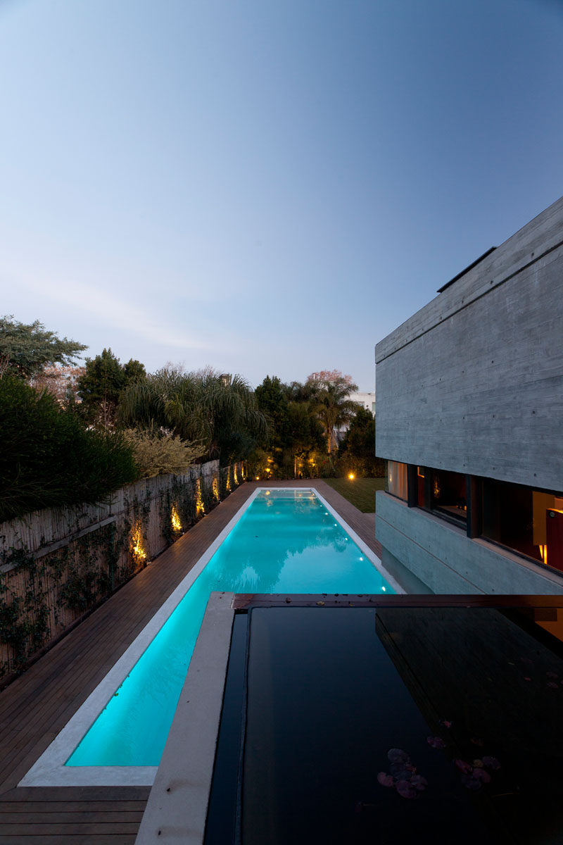 This modern concrete house has a linear swimming pool surrounded by a wood deck. #ConcreteHouse #ModernHouse #SwimmingPool