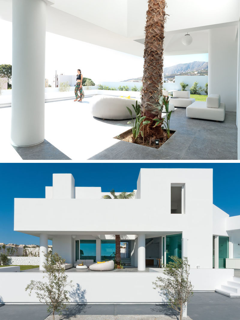 This modern house in Santorini has a partially covered outdoor lounge with a tall palm tree. #OutdoorSpace #OutdoorLounge #ModernArchitecture