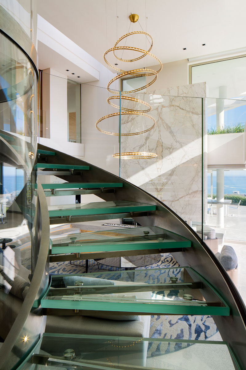 To reach the upper floors of this modern house, there's a triple volume glass lift that's surrounded by a circular glass and steel staircase. An LED metal pendant light fitting by Quasar Citadel compliments the staircase perfectly with its circular cascade design. #SpiralStaircase #GlassStaircase #SculpturalLighting