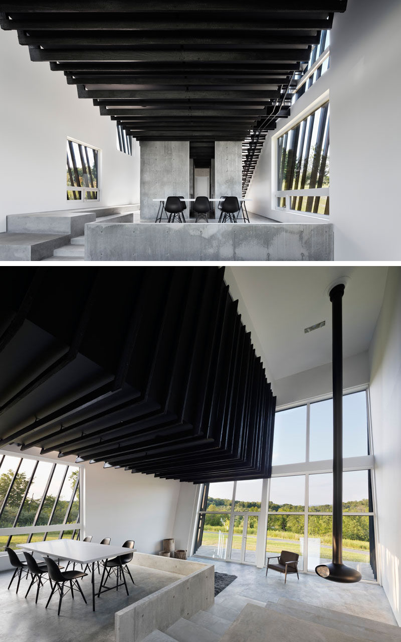 Continuing with the simple black and white color theme throughout this modern house, the dining room features a white dining table with a black base to match the black chairs and ceiling #ShouSugiBan #InteriorDesign #Windows #ModernDiningRoom