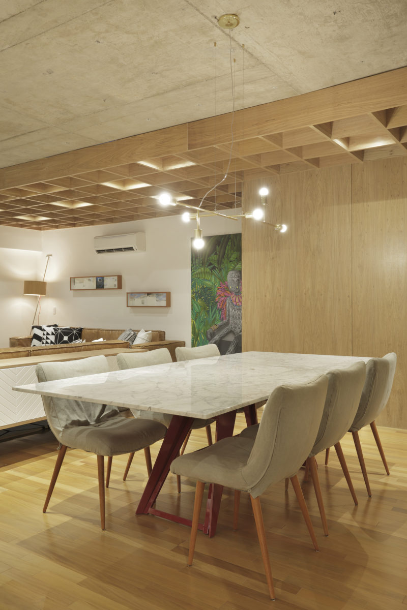 In this modern apartment, a minimalist chandelier hangs above a white dining table with natural colored chairs. #DiningRoom #ModernDiningRoom #InteriorDesign