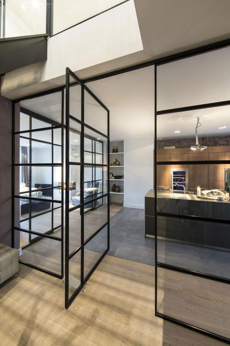 This modern apartment has a pivoting door within a black-framed glass wall. #InteriorDesign #PivotingGlassDoor #PivotingDoor #GlassWall