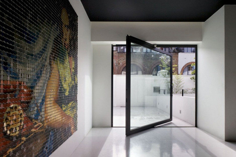 This square, pivoting glass door with a thick black frame leads out to a private patio area. #PivotingGlassDoor #GlassDoor #PivotingDoor