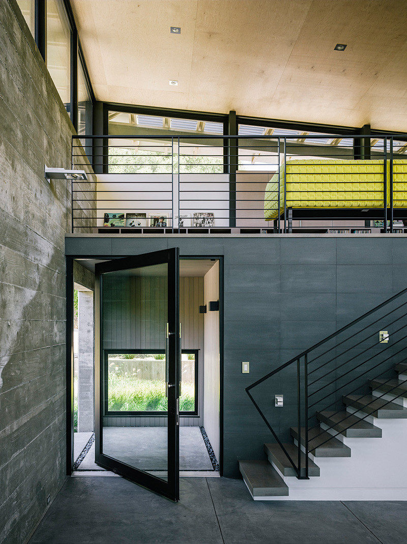A pivoting glass door welcomes you to this modern house, and the black frame matches the handrails and window frames. #PivotingGlassDoor #PivotingDoor #FrontDoor