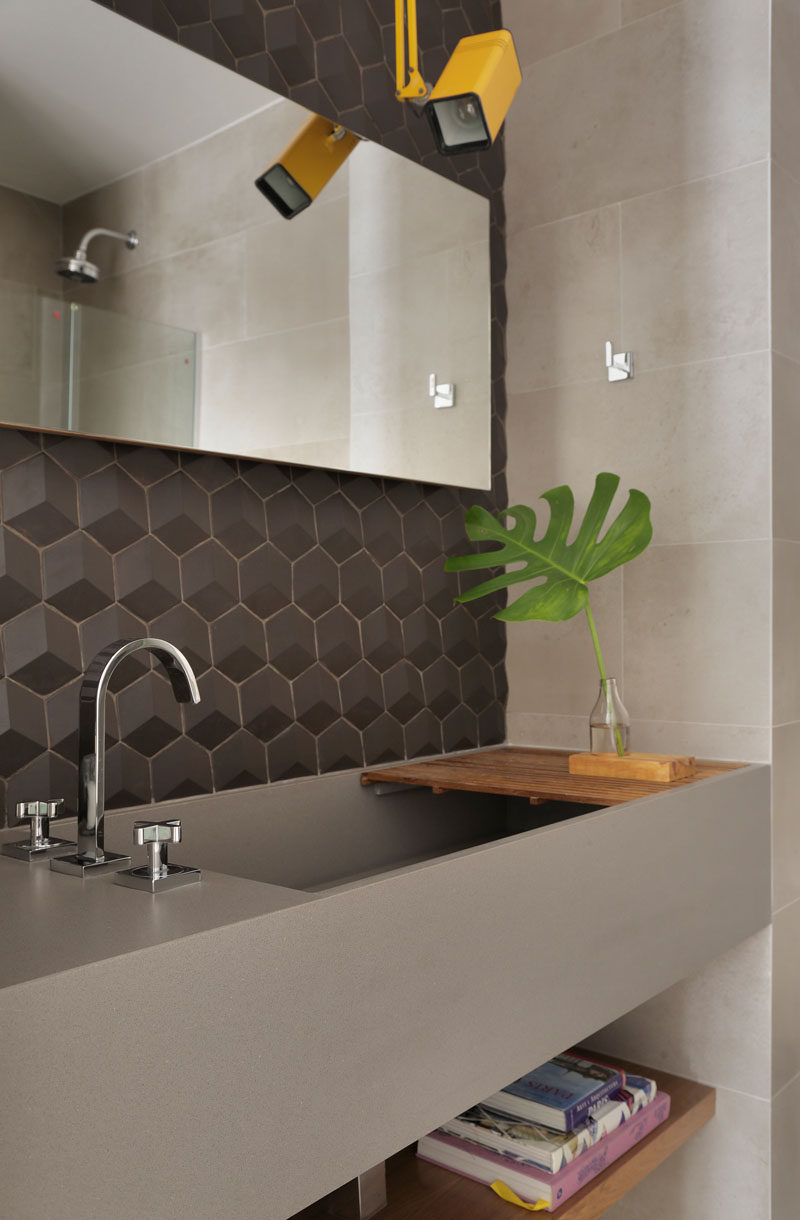 Grey tiles and a grey vanity with a large deep sink set the tone for this modern bathroom. A pop of color has been added with the use of a single yellow light. #ModernGreyBathroom #ModernBathroom #BathroomDesign