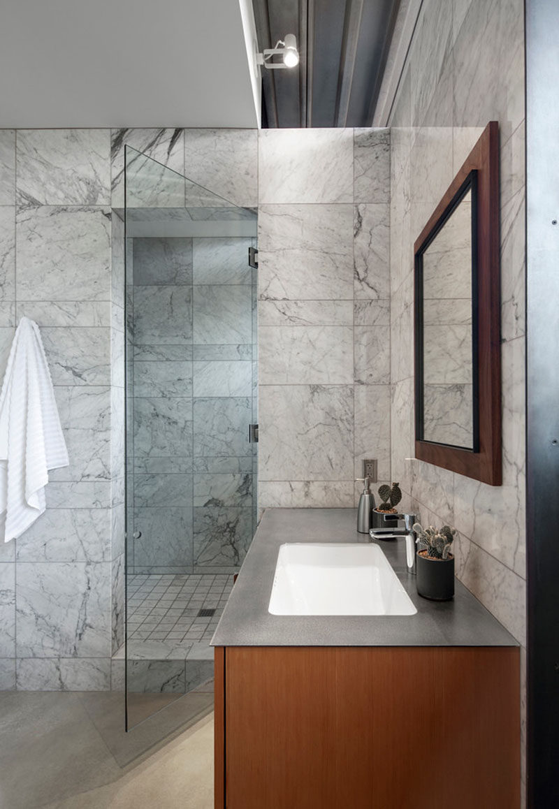 In this modern bathroom, simple grey tiles have been combined with a grey counter and wood to create a contemporary appearance. #GreyTiles #Wood #ModernBathroom