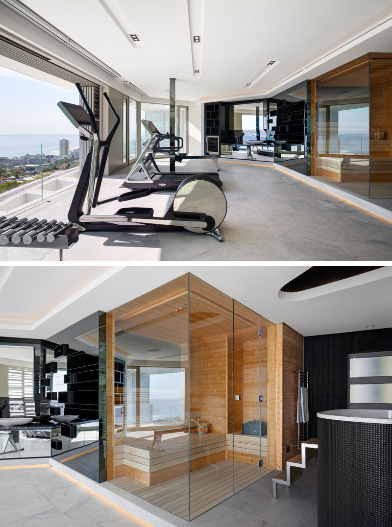 In this modern home gym, there's a spa bathroom with a sauna and chiller bath. Mirrors above a vanity reflect the view outside. #ModernHomeGym #Sauna #ModernGym
