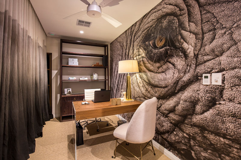 In this modern home office, a large animal mural fills an entire wall, while the curtains on the opposite wall compliment the colors found in the mural. #Mural #AnimalMural #HomeOffice #ModernInteriorDesign
