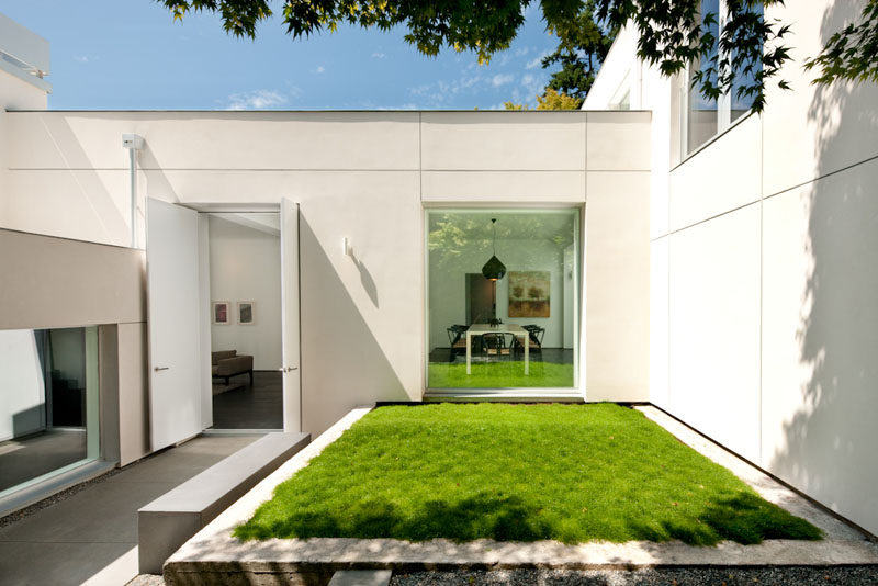 A small courtyard with grassy patch welcomes you to this modern house. #Landscaping #Architecture