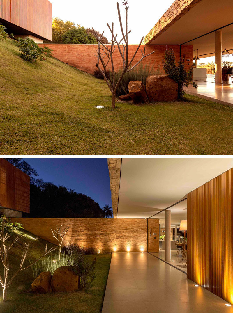 Upon entering this modern house, there's a grassy hill with a few plants and boulders. A covered path leads to the social areas of the home. #Landscaping #Architecture