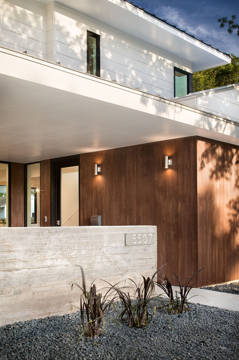 This modern house has a covered entry way that provides shelter when entering the front door. #ModernArchitecture #ModernHouse #WoodSiding