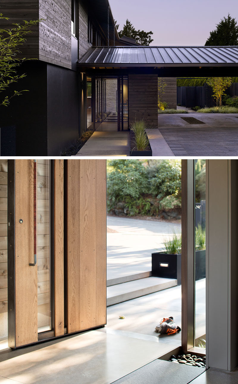 Upon arriving at this modern house, there's a carport that has views of a courtyard and a path provides access to the deck around the side of the home. A large wood and glass front door greets visitors. #Carport #ModernHouse #WoodFrontDoor #ModernFrontDoor