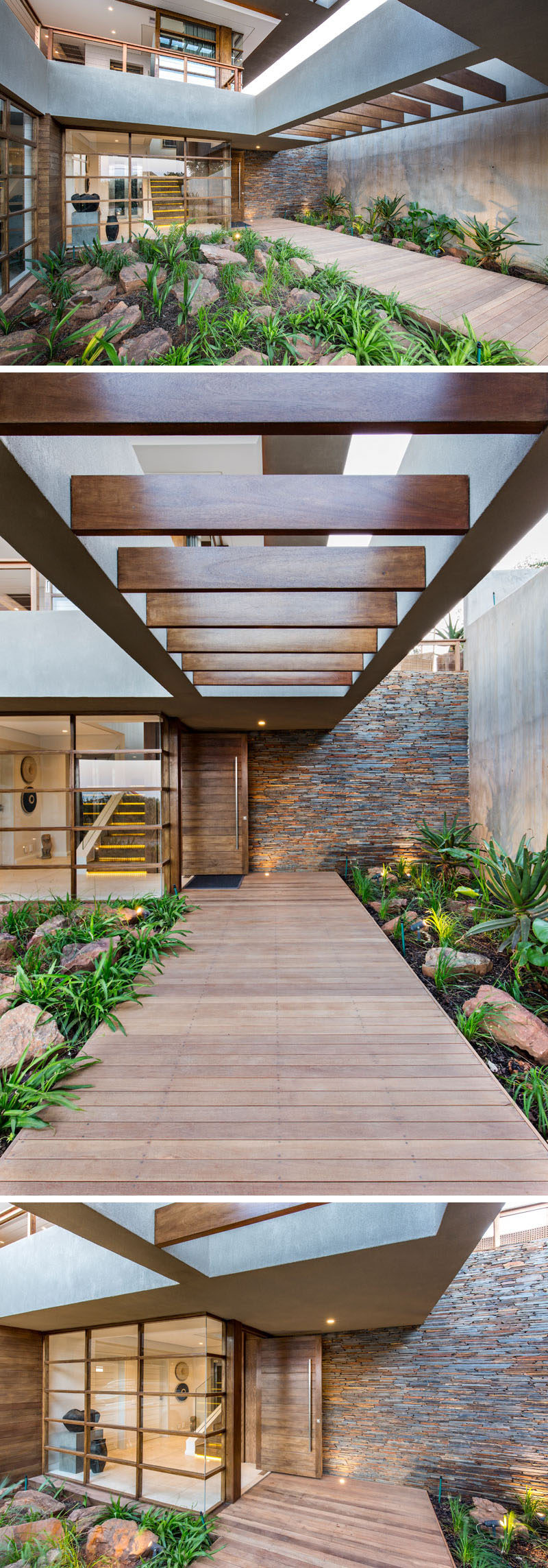 At the front of this modern house and off to the side, there's a wood walkway surrounded by plants and rocks, that leads to the front door. #Landscaping #Architecture #FrontEntrance #ModernHouse #WoodPath
