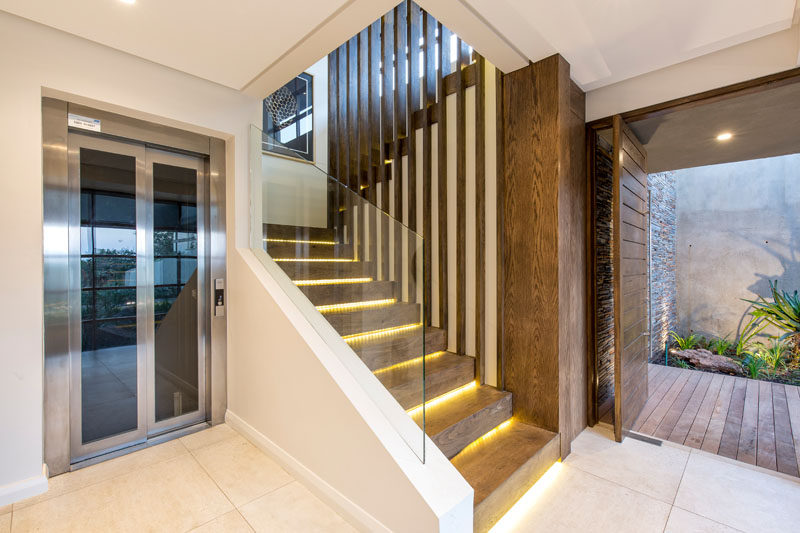 These modern wood stairs with hidden lighting and glass safety railings lead to the main floor of this house. #Stairs #HiddenLighting #ModernStairs