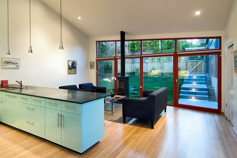 A small backyard is located of the living room in this modern house, with large doors providing access to the outdoor space. #Windows #Backyard #InteriorDesign #LightBlueKitchen